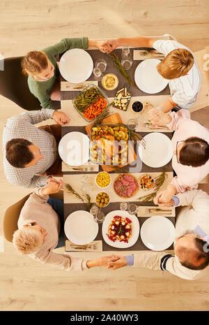 Angolo di Alta Vista della grande famiglia seduti al tavolo da pranzo per mano e pregando insieme prima di mangiare il pasto al giorno del Ringraziamento vacanza