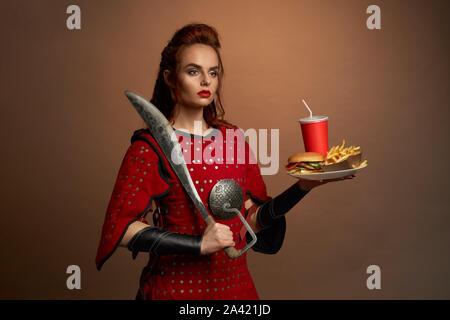 Bella combattente donna in red armor mantenendo il coltello di grosse dimensioni e la piastra con fast food in studio. Determinata la donna cerca riposo e posa con hamburger e libera di patate. Concetto di cibo di eroi.