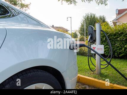 Tesla auto elettrica, E-auto carica presso la stazione di ricarica con cavo di ricarica, Bussolengo, Veneto, Italia, Europa
