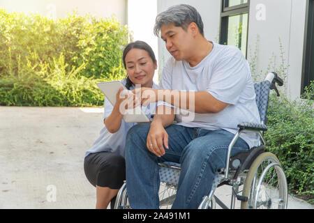 Il paziente causate da un incidente di automobile seduto in una sedia a rotelle e sua moglie è accanto e tenendo un tablet fargli guardare per rilassarsi passeggiando nel