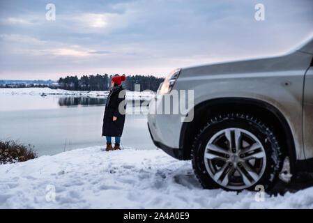 Giovane donna adulta in inverno abiti con Red Hat con bubo in piedi accanto a AUTO suv presso il River Side con bella vista Foto Stock