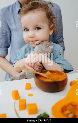 La ragazza abbracci giocattolo e pronto a mangiare la zucca Foto Stock
