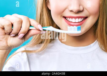 Giovane bella donna è impegnato nella pulizia dei denti. Bel sorriso Denti sani denti bianchi. Una ragazza detiene uno spazzolino da denti. Il concetto di igiene orale Foto Stock