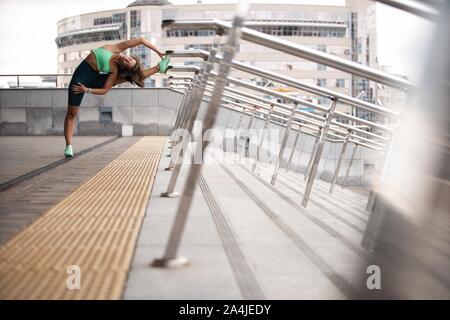Runner donna stretching muscolare delle gambe prima di eseguire all'aperto per l'atleta della formazione. Foto Stock
