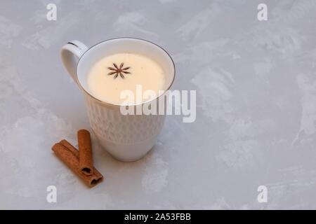 La tazza di caldo masala tea (chai) con anice stellato e bastoncini di cannella su uno sfondo grigio con spazio di copia Foto Stock