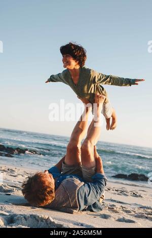 Padre figlio di sollevamento a metà in aria con le gambe sulla spiaggia Foto Stock