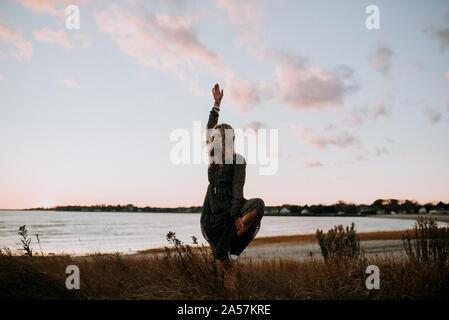 Donna fare yoga sulla spiaggia al tramonto Foto Stock