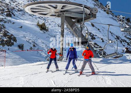 Pirenei, Andorra - 13 febbraio 2019: tre di sciatori in abiti colorati a piedi fuori la seggiovia verso l'alto. Coperte di neve e di pendenza per strutture metalliche Foto Stock