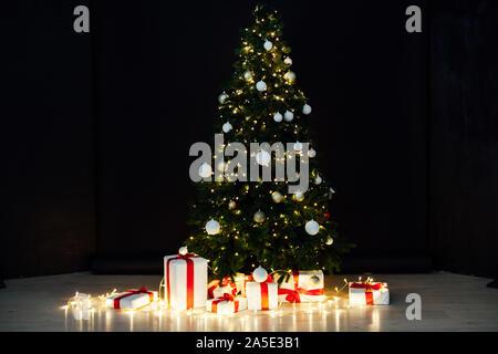 Le luci di Natale con albero di Natale e regali su sfondo nero
