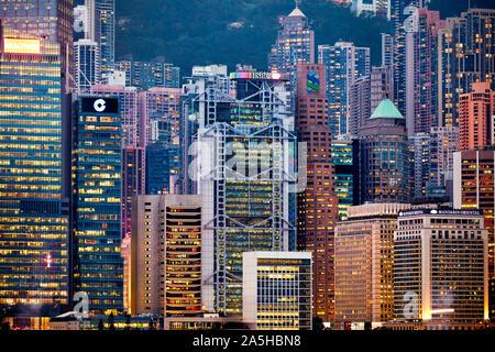 Edifici alti e moderni sul fronte acqua centrale illuminati di notte. Hong Kong, Cina.
