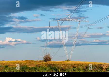Linee elettriche ad alta tensione e torri attraversare la campagna Foto Stock