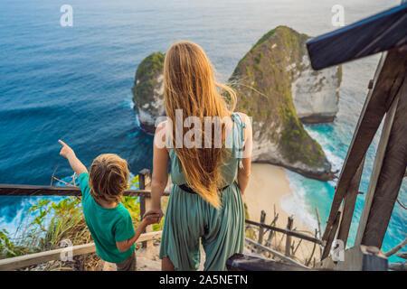 Vacanza per la famiglia stile di vita. Felice madre e figlio di stand a Viewpoint. Guardare bella spiaggia sotto la rupe alta. Destinazione di viaggio a Bali. Popolari Foto Stock