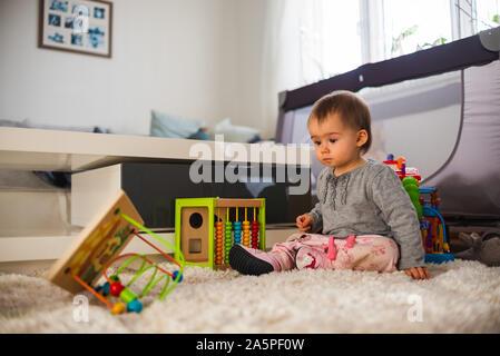 Carino piccolo bambino gioca con i giocattoli in salotto su un pavimento moquette. Foto Stock