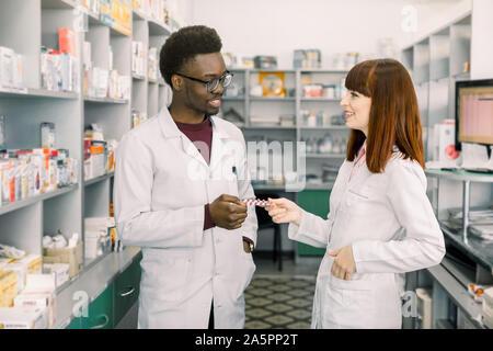 Fiducioso maschio e femmina farmacisti in farmacia. Africana di uomo e donna caucasica holding blister di pillole permanente, mentre in farmacia moderna