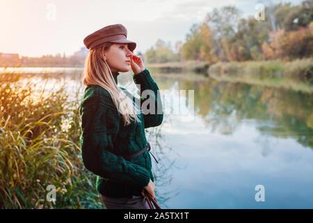 Autunno moderna moda. Giovane donna che indossa un maglione elegante vestito e hat dal fiume. Abbigliamento e accessori Foto Stock