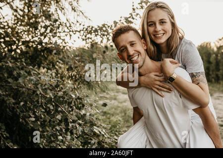 Ritratto di giovane coppia sorridente, uomo donna porta sul retro Foto Stock