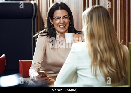 Ritratto di una donna felice con un amico in una caffetteria