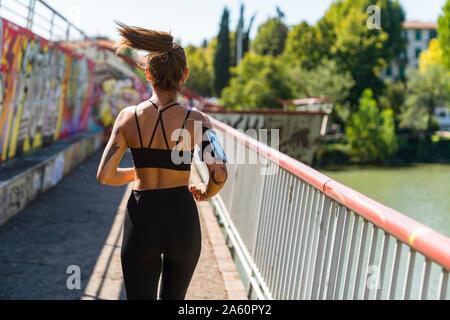 Vista posteriore della giovane donna in esecuzione su un ponte Foto Stock