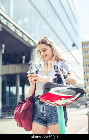 Ritratto di sorridente giovane donna appoggiata sul manubrio di E-Scooter tramite telefono cellulare, Berlino, Germania Foto Stock