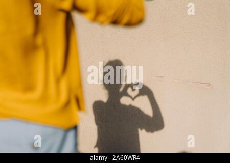 Ombra di una donna di sagomatura di un cuore con le mani Foto Stock
