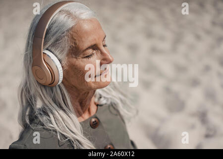 Senior donna ascoltando musica con le cuffie sulla spiaggia