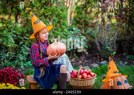 Carino bambina abbraccia una zucca in giardino d'autunno. Celebrando raccolto autunnale. Foto Stock