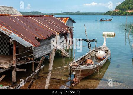 La barca a palangari di pesca tailandese accanto alla capanna del pescatore che si trova su palafitte in acqua. Tetto in sacchi arrugginito. Un pescatore versa l'acqua da una barca. Grande boa.