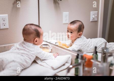 Adorabili 5 mese vecchio asian baby boy vedendo auto nello specchio del bagno a casa
