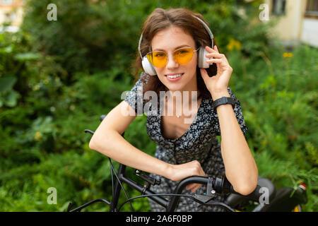 Un Ritratto di giovane donna caucasica con Perfect Smile, labbra carnose, bicchieri, auricolari, passeggiate nella natura e un giro in bici
