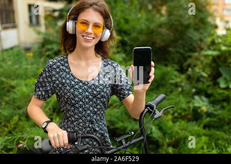 Un Ritratto di giovane donna caucasica con Perfect Smile, labbra carnose, bicchieri, auricolari, passeggiate nella natura, un giro in bici e mostra un telefono
