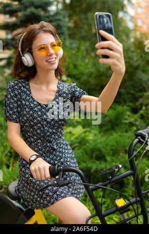 Giovane donna caucasica con Perfect Smile, labbra carnose, bicchieri, auricolari, passeggiate nella natura, un giro in bici e registra un video, fare selfie