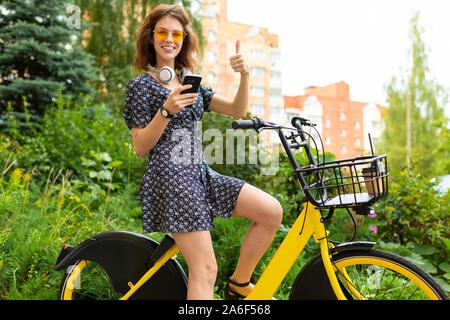 Giovane donna caucasica con Perfect Smile, labbra carnose, bicchieri, auricolari, passeggiate nella natura, un giro in bici, detiene un phne e lei piace