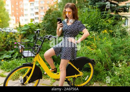 Giovane donna caucasica con Perfect Smile, labbra carnose, bicchieri, auricolari, passeggiate nella natura, un giro in bici e detiene un telefono e doubhts