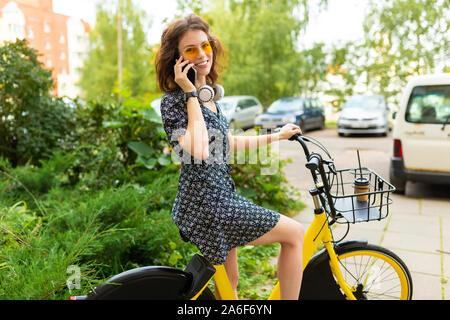 Giovane donna caucasica con Perfect Smile, labbra carnose, bicchieri, auricolari, passeggiate nella natura, un giro in bici e chiamare il telefono