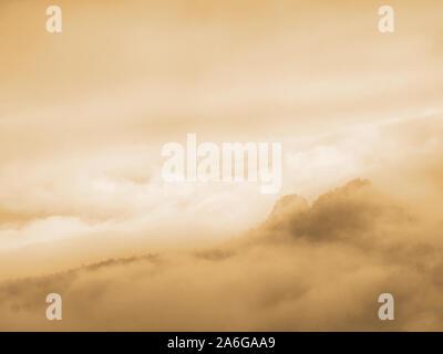 La nebbia nel paesaggio collinare. Autunno cremosa di nebbia in campagna. Hill è aumentata dalla nebbia la nebbia è colorato di oro e blu Foto Stock