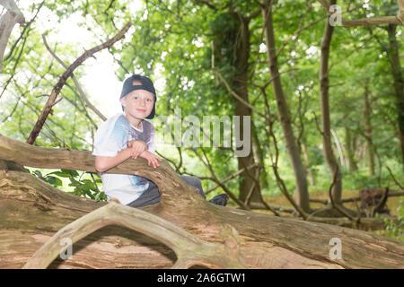 Un cheeky poco ragazzo seduto in un cornfield indossando un cappello da baseball, mentre fuori a giocare con gli amici Foto Stock