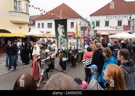Un cavaliere di indossare la corazza e la sua signora camminando mano nella mano, guardato dal pubblico, Eggenburg Festival medievale, Austria il più grande evento medievale