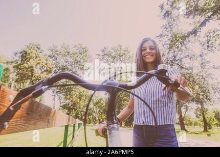 Ritratto di felice attraente giovane donna in jeans corti con la bicicletta nel parco il giorno d'estate. Basso angolo di visione. Foto Stock