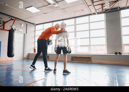 Felice positivo allegro coach cheerfing il ragazzo alto prima del combattimento, supporto , a lunghezza piena vista posteriore foto. spazio copia Foto Stock