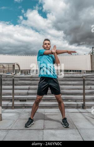 Athletic uomo, pomeriggio estivo di formazione in città, uno stile di vita attivo e moderno allenamento fitness, sportswear t-shirt shorts sneakers. Riscaldare i muscoli Foto Stock