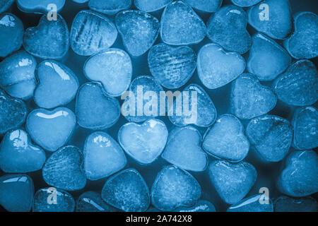 Cuori di ghiaccio su sfondo blu. Creative design minimalista. Scheda romantico con fresco congelato cuore. Astratta cornice in stile moderno. Texture brillanti, Foto Stock