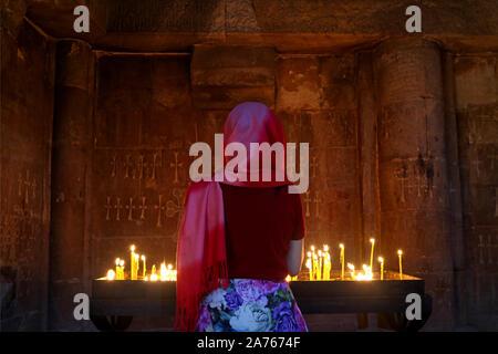 Donna in testa che copre in preghiera nella chiesa ortodossa