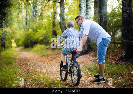 Giovane padre insegnando il suo figlio ad andare in bicicletta
