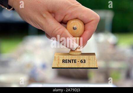 Mano mit Stempel, Frauenhand, Aufschrift: Rente mit 63 Foto Stock