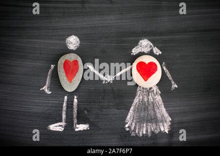 Ciottoli con cuori rossi all'interno di creta disegno di un uomo e di una donna sulla lavagna. Close-up.