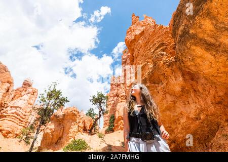 Giovane donna in piedi guardando il paesaggio del deserto vista estiva nel Parco Nazionale di Bryce Canyon su loop Navajo ampio angolo con la fotocamera e il cielo