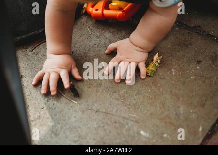 Carino baby mani esplorare in giardino Foto Stock