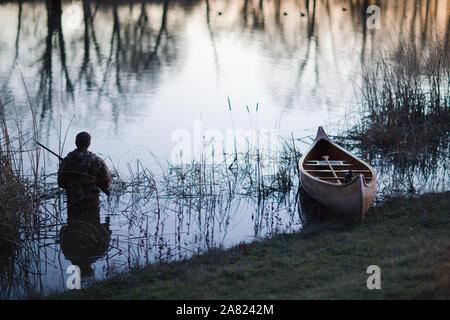 Uomo con un fucile da caccia in acqua accanto a una canoa. Foto Stock