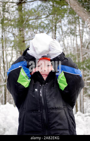 Con le braccia sollevate, questo bambino è pronto a lanciare una palla di neve a voi Foto Stock