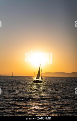 In barca a vela sulla baia di San Francisco al tramonto con il Golden Gate bridge Foto Stock